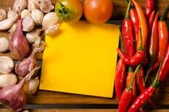 Nota amarilla con los chiles, el tomate, el chalote y el ajo en el fondo de madera Imagen de archivo libre de regalías