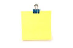 Nota amarilla con un clip de la carpeta Foto de archivo libre de regalías