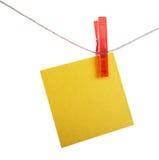 Nota amarilla del recordatorio que cuelga en un clothespin rojo Foto de archivo libre de regalías