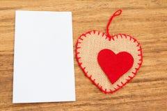 Nota appiccicosa in bianco con un cuore rosso su un fondo di legno Fotografia Stock