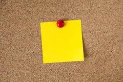 Nota appiccicosa di ricordo giallo sul bordo del sughero, spazio vuoto per testo Immagini Stock Libere da Diritti