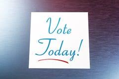 Nota appiccicosa di voto sopra per la menzogne di carta di oggi sull'alluminio spazzolato del frigorifero Immagini Stock