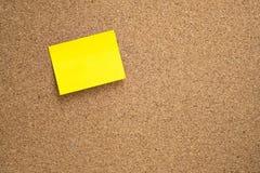 Nota appiccicosa gialla incollata sul bordo marrone del sughero Immagine Stock Libera da Diritti