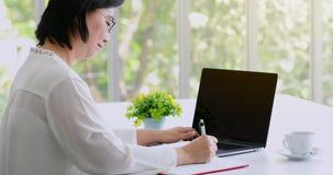Nota asiática mayor de la escritura de la mujer sobre el cuaderno almacen de metraje de vídeo