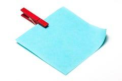 Nota azul do lembrete com os pinos de roupa da cor Fotografia de Stock