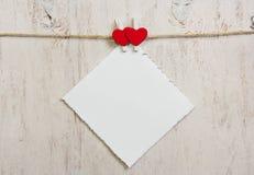 Nota in bijlage met twee rode hartenwasknijpers Royalty-vrije Stock Afbeelding