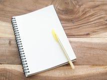 Nota blanca con la pluma del yellw en la tabla de madera Fotografía de archivo libre de regalías