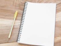 Nota blanca con la pluma del yellw en la tabla de madera Imágenes de archivo libres de regalías