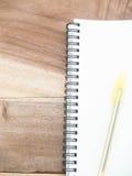 Nota blanca con la pluma del yellw en la tabla de madera Fotos de archivo