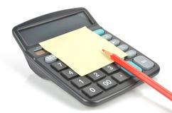 Nota, calculadora y lápiz de post-it Imagen de archivo libre de regalías
