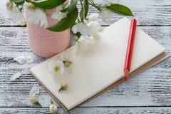 A nota, cartão, escrevendo floresce em uma tabela de madeira do vintage Flores cor-de-rosa da mola Fotografia de Stock