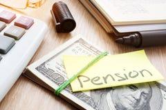 Nota con la pensión de la palabra en una pila de dinero Plan de retiro foto de archivo libre de regalías