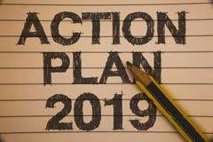 Nota da escrita que mostra o plano de ação 2019 Objetivos apresentando das ideias do desafio da foto do negócio para que a motiva fotografia de stock