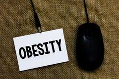 Nota da escrita que mostra a obesidade O excesso apresentando do problema médico da foto do negócio de gordura corporal acumulou  Fotografia de Stock Royalty Free