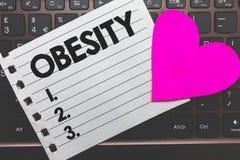 Nota da escrita que mostra a obesidade O excesso apresentando do problema médico da foto do negócio de gordura corporal acumulou  Foto de Stock Royalty Free