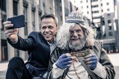 Nota de dólar de beijo desesperada do ancião pobre quando homem de sorriso que faz a foto fotos de stock royalty free