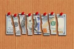 A nota de dólar dos E.U. cortou nas partes que sugerem a economia fraca dos E.U. Fotografia de Stock Royalty Free