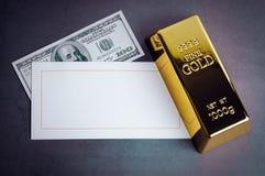 Nota de dólar e cartão do lingote do lingote da barra de ouro fotografia de stock