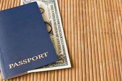 1 nota de dólar em um passaporte azul em um guardanapo de bambu Imagens de Stock Royalty Free