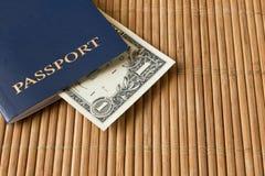 1 nota de dólar em um passaporte azul em um guardanapo de bambu Fotos de Stock