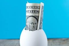 1 nota de dólar em um shell de ovo Em um fundo de turquesa O co Fotografia de Stock Royalty Free