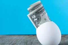 nota de dólar 2 em um shell de ovo Em um fundo de turquesa O co Foto de Stock Royalty Free