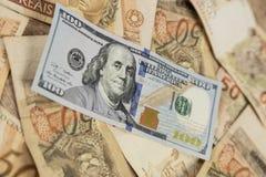 Nota de 100 dólares encima de 50 notas de los reais Imagen de archivo libre de regalías