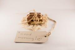 Nota de la buena mañana, chocolate en un fondo blanco Imagenes de archivo