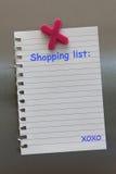 Nota de la lista de compras sobre una puerta del refrigerador con el imán foto de archivo libre de regalías