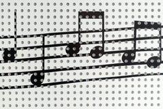 Nota de la música sobre la pared blanca Imagen de archivo