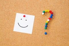Nota de la sonrisa fijada al tablero del cordón. Imagen de archivo