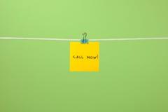 A nota de papel amarela na corda com texto chama agora! Imagens de Stock