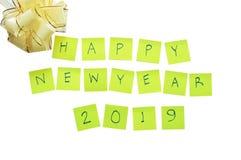 Nota de papel amarela que escreve o ano novo feliz 2019 e a curva da fita no fundo branco Fotografia de Stock