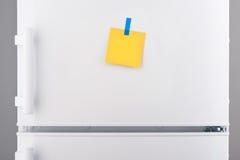 Nota de papel amarela vazia e etiqueta azul no refrigerador branco Imagens de Stock Royalty Free