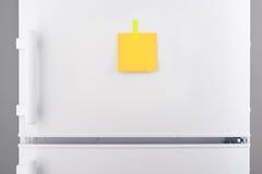 Nota de papel amarilla atada con la etiqueta engomada en el refrigerador blanco Imágenes de archivo libres de regalías