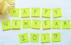 Nota de papel amarilla que escribe la Feliz Año Nuevo 2019 y el arco de la cinta en el fondo blanco Fotografía de archivo