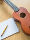 Nota de papel con el ukelele, concepto para la escritura de la música Foto de archivo