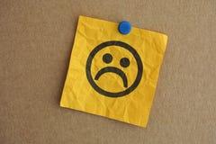 Nota de papel con la cara triste Fotografía de archivo libre de regalías
