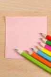 Nota de papel con los lápices coloreados Foto de archivo