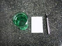 Nota de papel vacía con el vidrio del agua y de la pluma en la tabla Imagen de archivo libre de regalías