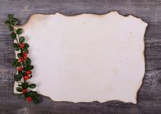 Nota de papel vazia para Santa Claus com as bagas vermelhas na parte traseira de madeira Imagens de Stock