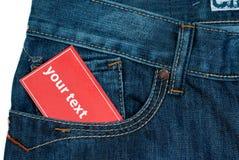 Nota de papel vermelha no bolso das calças de brim fotografia de stock