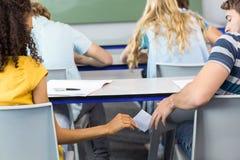 Nota de passagem do estudante fêmea ao amigo na sala de aula fotografia de stock