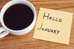 Nota de post-it con la escritura del hola enero y de la taza de café imágenes de archivo libres de regalías