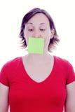 Nota de post-it de la mujer joven sobre su boca Fotos de archivo