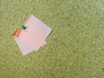Nota de post-it vazia fixada a uma placa/quadro de mensagens da cortiça Fotografia de Stock