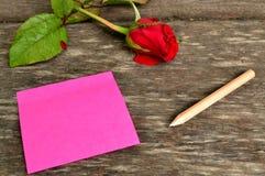 Nota de post-it y rosa rosadas del rojo Fotos de archivo libres de regalías