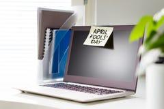 Nota del día del ` de April Fools sobre el ordenador portátil en el trabajo fotos de archivo libres de regalías