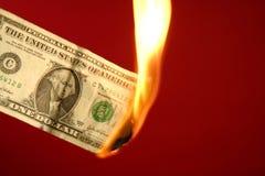 Nota del dollaro che brucia in fuoco sopra colore rosso Immagine Stock