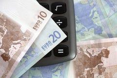 Nota del euro diez y veinte sobre una calculadora Foto de archivo libre de regalías